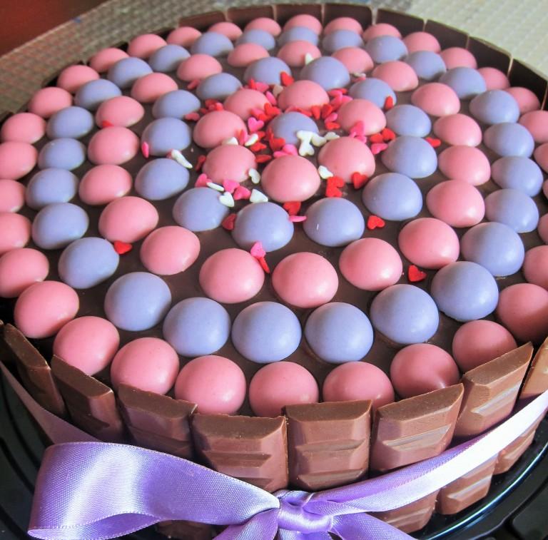 Torta de vainilla rellena con ganache de chocolate semi amargo y fresas Decoración: chocolatinas negras y esferas de chocolate blanco hechas en casa