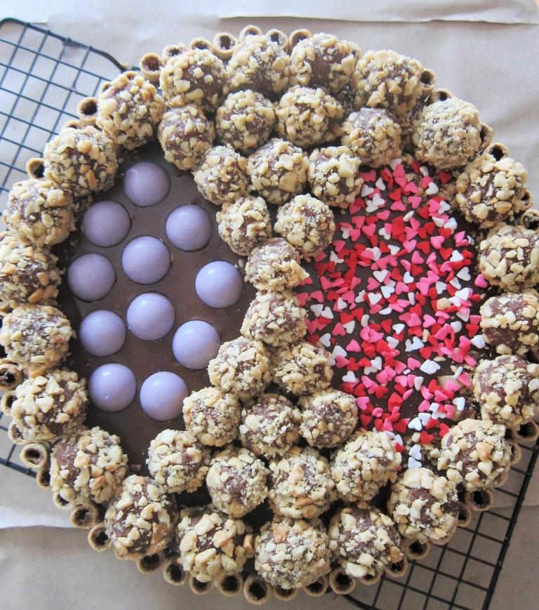 Torta de vainilla rellena y cubierta con ganache de chocolate Decoración: pirulines y/o barquillos con trufas de chocolate y esferas de chocolate blanco