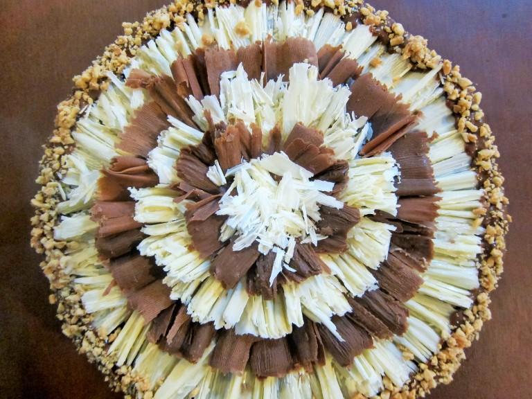 Torta de vainilla  rellena  y cubierta de arequipe Decoración: pirulines y/o barquillos con chocolate negro y blanco